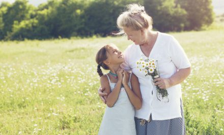40206104 - great-grandmother and granddaughter standing in flower field in sunlight