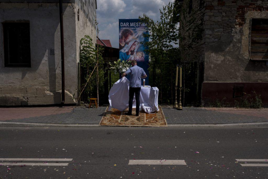 30 maja. Ulica Obrońców Poczty Gdańskiej. Jeden z mieszkańców sprząta jeden z ołtarzy po procesji Bożego Ciała.